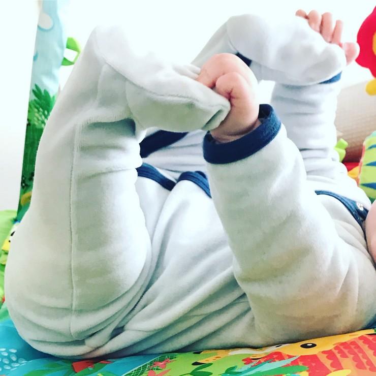 Bebe qui tient ses pieds