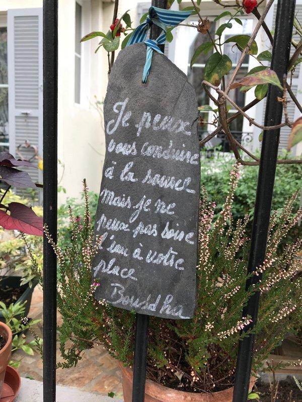 Citation sur plaque ardoise devant maison fleurie