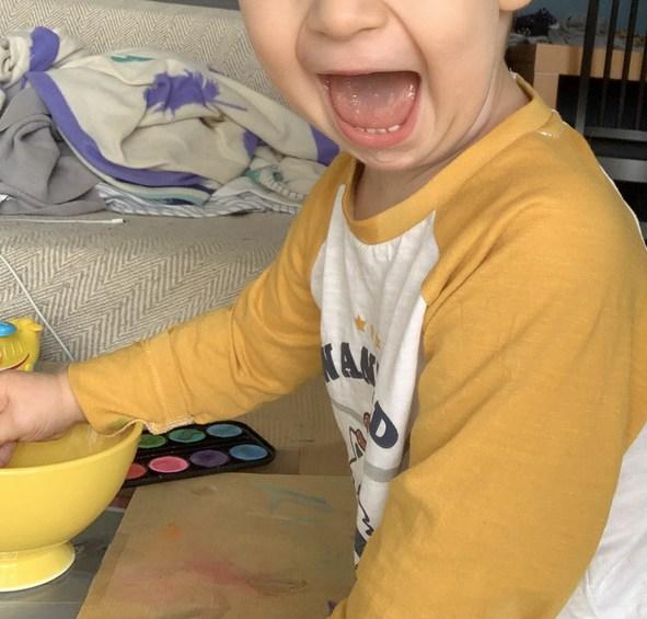 grand sourire pendant la séance de peinture à l'eau